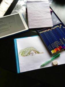 Foto på illustration av hund med pennor jämte