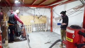 Två personer målar ett rum och har munskydd på sig