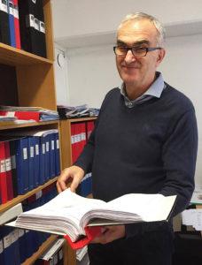 Aleksa vår ekonom står i sitt rum och håller en bokföringspärm
