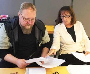 Rolf och Åsa sitter vid ett skrivbord och hjälper varandra mer bokföring