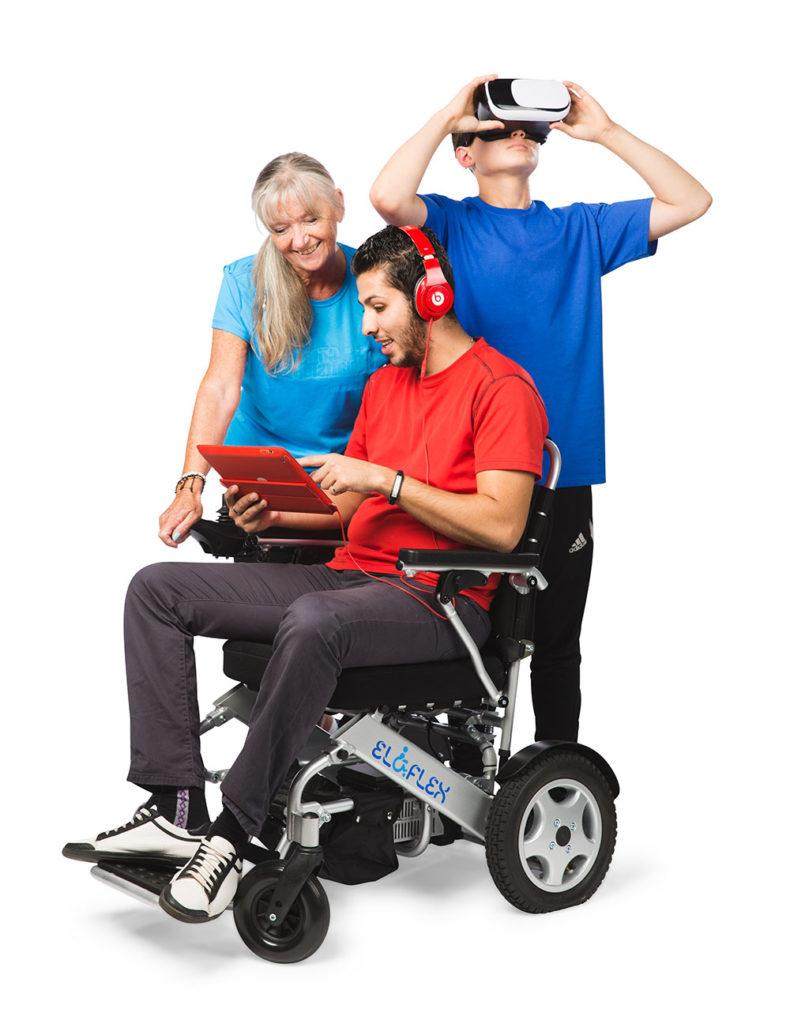 Ung man i elrullstol med surfplatta i handen, äldre kvinna tittar på, ung kille använder virtual reality