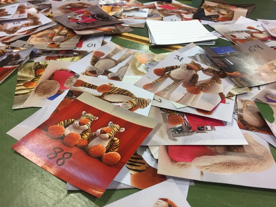 Många foton att använda till barnböcker ligger utspridda på ett bord