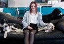 Hanna sitter i en soffa med två hundar